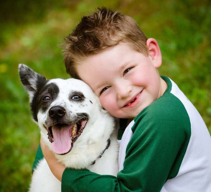 Young boy smiling and hugging his dog